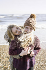 Two girls on the beach in winter.