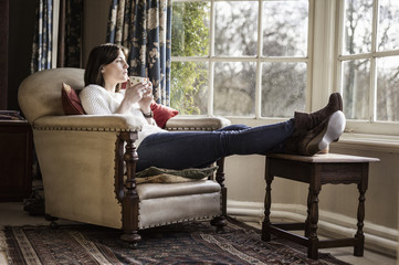 A young woman relaxing at home, with her feet up, having a cup of tea.