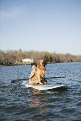 A child and a retriever dog sitting on a paddleboard on the water.