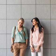 Couple of women portrait outdoors with modern tiled wall as back