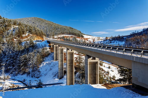 Foto op Canvas Mountain bridge in winter with snow and blue sky