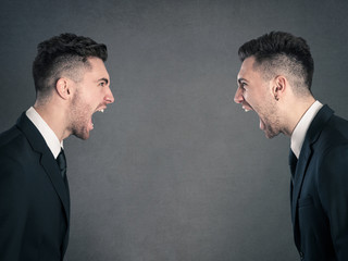 Two angry businessman facing each others. Studio portrait agains