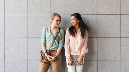 Couple of smiling women portrait outdoors with modern tiled wall