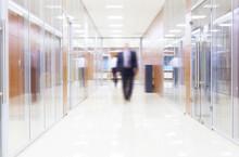 biznesmen idzie wzdłuż korytarza w nowoczesnym biurze