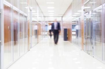 businessman goes along a corridor at modern office