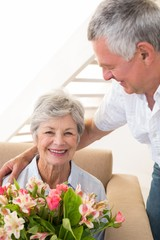 Senior man giving his partner a bouquet of flowers smiling at ca