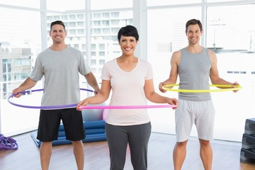 Fitness class holding hula hoops around waist in gym
