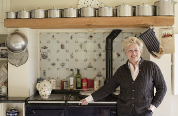 A woman standing with her back to a range cooker, in her kitchen.