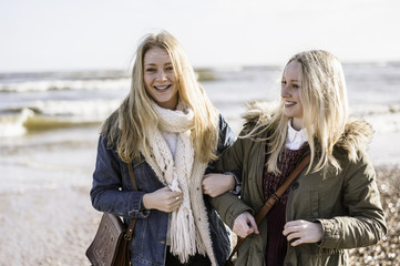 Two young girls on a beach in winter.