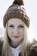 A young girl in a bobble hat on the beach.