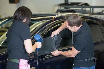 Car wrapping specialists wrapping side mirror with carbon foil