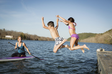 Two children leaping into the water from a jetty.