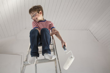 A boy seated on a stepladder.