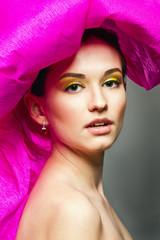 Девушка с ярким макияжем в розовой шляпе