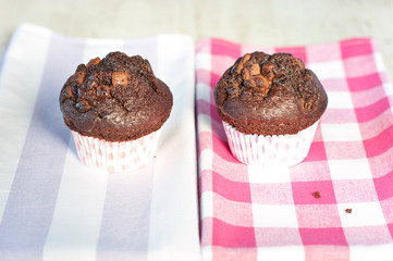 Delicious homemade chocolate muffins on checkered tablecloth