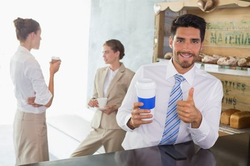 Businessman with coffee sipper gesturing thumbs up in office caf