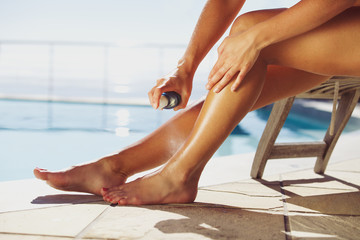 Woman spraying suntan lotion onto her leg by the pool