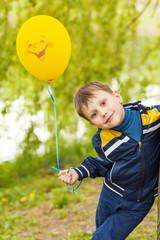 Smiling happy boy whith yellow balloon