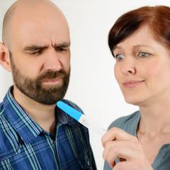 Erschrockenes Paar mit Schwangerschaftstest
