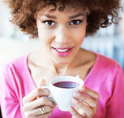 Afro woman with cup of tea