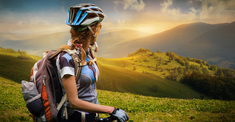 Young woman with bicycle standing in the mountains