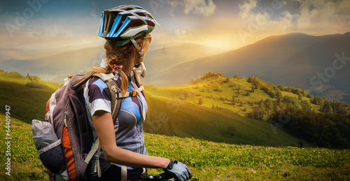 Papiers peints Cyclisme Young woman with bicycle standing in the mountains