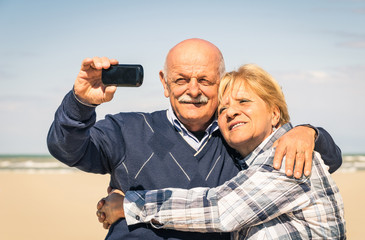 Senior happy couple taking a selfie at the beach