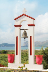 Greek Orthodox bell tower with the sea at the background