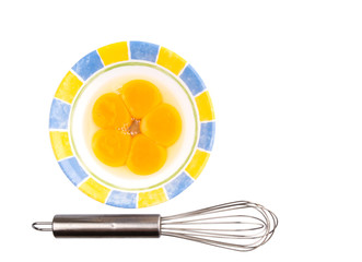 An egg beater with egg yolk in a ceramic bowl
