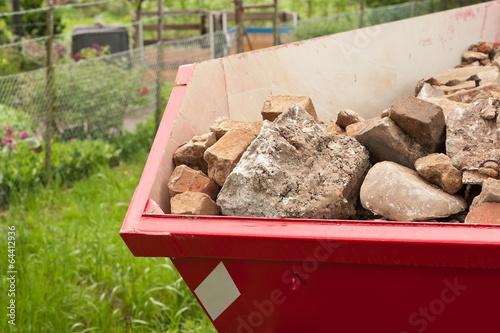 Ein roter Container gefüllt mit Bauschutt - 64412936