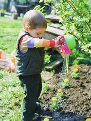 Трудолюбивый маленький мальчик работает в саду
