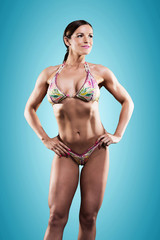Muscled fitness woman wearing bikini. Brown hair. Studio shot ag