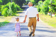 grandfather with his granddaughter are on the road