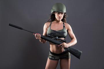 Muscled fitness army girl holding gun. Wearing green helmet. Stu