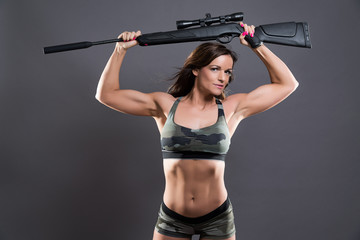 Muscled fitness army girl holding gun. Studio shot against grey.