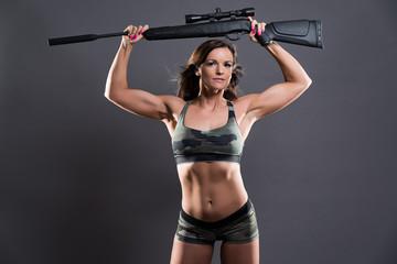 Muscled fitness army girl holding gun. Studio shot against grey.