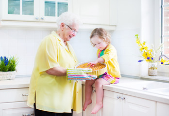 Great grandmother and little girl cooking pie in sunny kitche