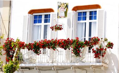 Balcón con flores en una fachada de Sitges, Barcelona
