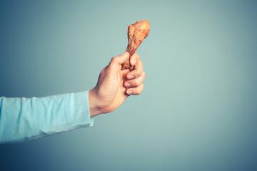 Man holding a chicken drumstick