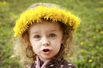 Little child with dandelion wreath