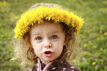 Little child with dandelion wreath
