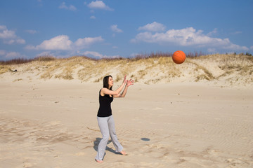 Girl playing beach basketball