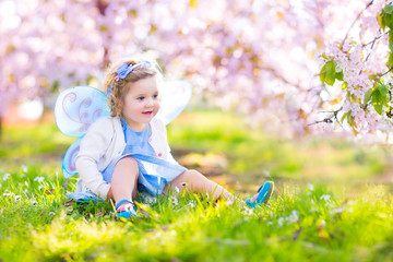 Beautiful toddler girl in fairy costume playing in cherry garden