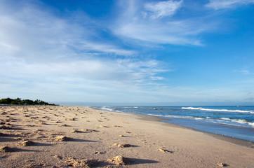 ocean and sandy beach on blue sky background