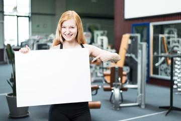Frau im Fitnessstudio hält Werbetafel