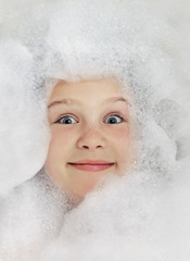 Happy baby in the bath, swimming in the foam