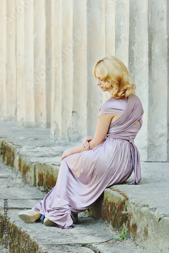 model sitting near old columns
