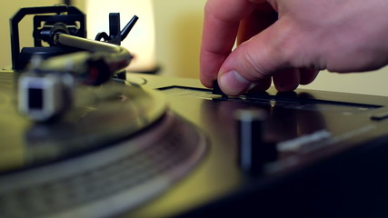 Male Hand Pushing Pitch Control Fader on Retro Turntable Vinyl