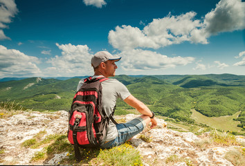 On the top of mountain. Man with backpack enjoyed with mountain