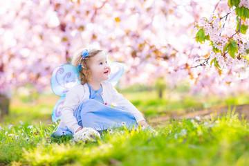 Curly toddler girl in fairy costume walking in fruit garden